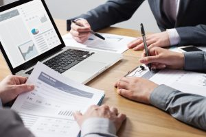 Business professionals working together at office desk hands close up pointing out financial data on a report teamwork concept