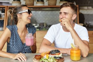 Two best friends having fun together and laughing while eating lunch at coffee shop. Attractive female holding glass of pink smoothie enjoying lively conversation with her handsome boyfriend - Photocopier Leasing Sheffield